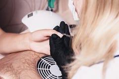 Bewegen Sie beiseite die Häutchennahaufnahme in einem Schönheitssalon Maniküreprozeß? Die Frauhände? stockbild