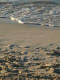 Bewegen Sie das Kommen in Ufer auf sandigem Strand wellenartig Stockfoto
