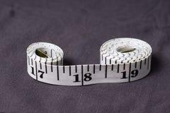 Bewegen Sie, der Zentimeterbandschneider schritt für schritt fort, der in Form von acht gefaltet wird Stockfoto