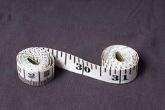 Bewegen Sie, der Zentimeterbandschneider schritt für schritt fort, der in Form von acht gefaltet wird Lizenzfreies Stockbild
