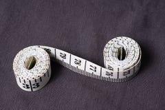 Bewegen Sie, der Zentimeterbandschneider schritt für schritt fort, der in Form von acht gefaltet wird Lizenzfreie Stockfotografie