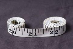 Bewegen Sie, der Zentimeterbandschneider schritt für schritt fort, der in Form von acht gefaltet wird Lizenzfreie Stockfotos