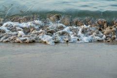 Bewegen Sie Rollen an der Küste über braunem Strandsand wellenartig Stockbild