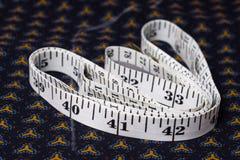 Bewegen Sie, Zentimeterband auf einem Hintergrund des blauen Gewebes mit einem patt Schritt für Schritt fort Stockbild