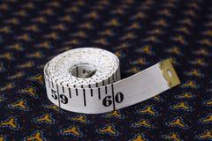 Bewegen Sie, Zentimeterband auf einem Hintergrund des blauen Gewebes mit einem patt Schritt für Schritt fort Stockfoto