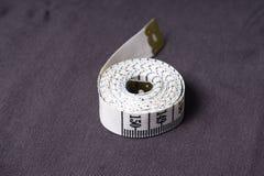 Bewegen Sie, Zentimeterband auf einem Hintergrund des grauen Gewebes Schritt für Schritt fort Lizenzfreie Stockfotografie