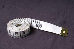 Bewegen Sie, Zentimeterband auf einem Hintergrund des grauen Gewebes Schritt für Schritt fort Lizenzfreies Stockbild