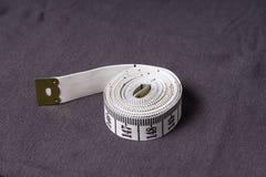 Bewegen Sie, Zentimeterband auf einem Hintergrund des grauen Gewebes Schritt für Schritt fort Lizenzfreie Stockfotos
