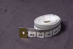 Bewegen Sie, Zentimeterband auf einem Hintergrund des grauen Gewebes Schritt für Schritt fort Stockbild