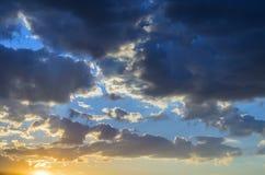 Bewegend über dem Horizont hinaus, belichtet die Sonne seine grauen Wolken der Strahlen, die auf dem Hintergrund des blauen Himme stockfotografie