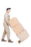 Bewegend de bagagekarretje van de leveringsmens met kartondozen Royalty-vrije Stock Fotografie