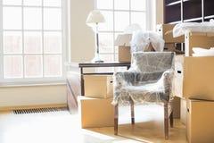 Bewegend dozen en meubilair in nieuw huis Stock Foto