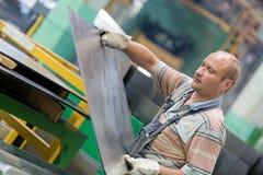 Bewegend het metaalblad van de fabrieksarbeider in workshop stock afbeeldingen