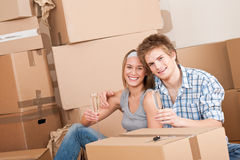 Bewegend huis: Het gelukkige man en vrouwen vieren Stock Fotografie