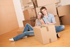 Bewegend huis: Het gelukkige man en vrouwen vieren Stock Foto's