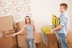 Bewegend huis: Man en vrouw met doos en stoel Royalty-vrije Stock Foto