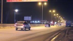 Bewegende auto's en bus dichtbij post, banners met verlichting bij donkere nacht stock videobeelden