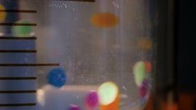 Bewegende bunte Pillen, Tabletten, Drogen, meds im Wasser an pharma Ausstellung stock footage