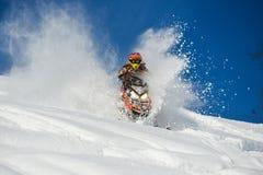 Bewegende sneeuwscooter in de winterbos in de bergen royalty-vrije stock afbeelding