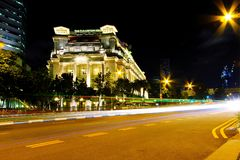 Bewegende verkeerslichtstaarten van vervoer bij nacht met Fullerton-hotelachtergrond in Singapore stock foto's