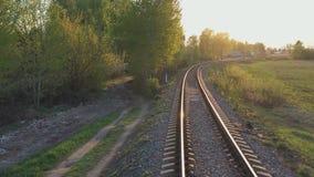 Beweging op een enkelsporige spoorweg in de stralen van de het plaatsen zon stock video