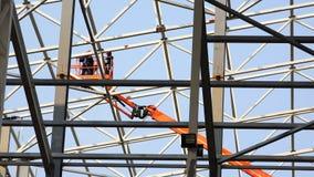 Beweging van arbeiders bij een hoogte in de lift tussen de structuren van metaal stock video