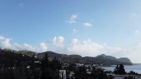 Beweging van wolken over een kleine stad onder de bergen stock videobeelden