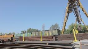 Bewegingen van een de grote gele brugkraan rond het pakhuis met metaal, een brugkraan tegen de blauwe hemel
