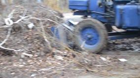 Bewegingen van het bulldozer drogen de kleine graafwerktuig takken en gras op stadsstraten stock footage