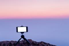 Bewegliche Fotografie des intelligenten Telefons auf dem felsige Berghintergrund Stockfoto