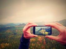 Bewegliche Fotografie des intelligenten Telefons der nebelhaften Landschaft Fokussieren Sie, um mit Telefon in den Mannhänden ein Stockfotos