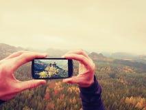 Bewegliche Fotografie des intelligenten Telefons der nebelhaften Landschaft Fokussieren Sie, um mit Telefon in den Mannhänden ein Lizenzfreies Stockfoto