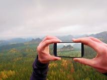 Bewegliche Fotografie des intelligenten Telefons der nebelhaften Landschaft Fokussieren Sie, um mit Telefon in den Mannhänden ein Stockfoto