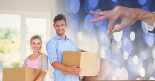 bewegliche Kästen der Leute in neues Haus mit Schlüssel Lizenzfreies Stockbild