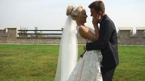 Bewegliche Kamera in Richtung zu den jungen attraktiven Jungvermähltenpaaren in der Liebe, die zart im schönen Garten umarmt stock footage