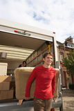 Bewegliche Paare, die Sofa From Truck entladen lizenzfreies stockbild