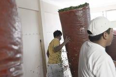 Beweglicher großer Sack der Arbeitskraft voll der Koka verlässt bei Coca Leaves Depot in Chulumani Stockbild