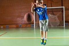 Beweglicher kleiner Junge, der einen Basketball aufprallt Stockbilder