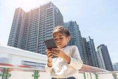 Beweglicher on-line-Ohrenpfropfen des asiatischen städtischen Kinderlebensstilsüchtigen stockfotos
