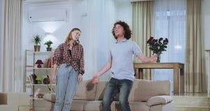 Beweglicher Tag für ein junges attraktives Paar sie das große Sofa im Leben tragend sehr aufgeregte auf unten fallen stock video footage