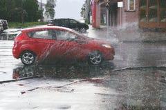 Bewegliches Auto sprüht eine Pfütze, wenn starker Regen fällt Lizenzfreie Stockfotografie