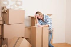 Bewegliches Haus: Frau mit Kasten im neuen Haus Stockfotografie