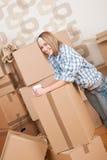 Bewegliches Haus: Frau mit Kasten im neuen Haus Lizenzfreies Stockbild