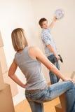 Bewegliches Haus: Hängende Borduhr der jungen Paare auf Wand lizenzfreies stockbild