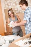 Bewegliches Haus: Junge Paare, die Teller entpacken Stockfoto