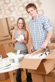 Bewegliches Haus: Junge Paare, die Teller entpacken stockfotos
