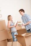 Bewegliches Haus: Junge Paare mit Kasten im neuen Haus Stockbilder