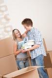 Bewegliches Haus: Junge Paare mit Kasten im neuen Haus Stockfoto