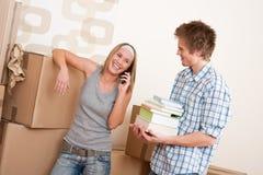 Bewegliches Haus: Junge Paare mit Kasten im neuen Haus Stockfotografie