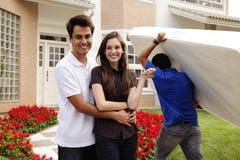 Bewegliches Haus: Paare infront des neuen Hauses Stockfotos